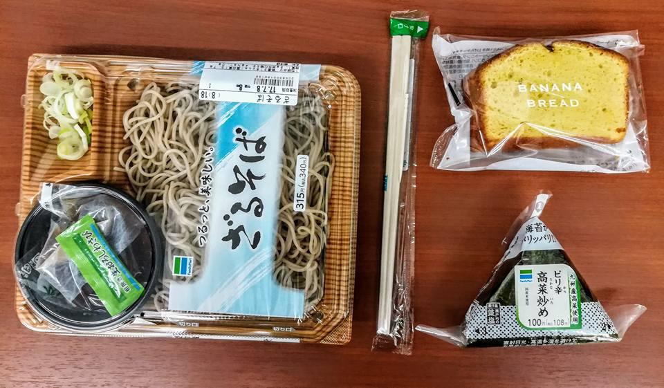 """Repas du soir dans un kombini. Ça a été toute une aventure que de savoir à quoi était fourré l'onigiri (le triangle de riz recouvert d'algue en bas à droite, pardon pour les initiés, mais je préfère traduire pour l'ancienne génération qui me lit). J'ai dû apprendre un peu de grammaire japonaise pour me renseigner, puisqu'aucun mot anglais ne figurait sur l'étiquette. Une dame m'a donc expliqué hier que ma boulette de riz ne contenait pas de viande, mais du """"tsukemono"""", ce qui ne m'avancait pas beaucoup plus que vous. J'ai alors mobilisé les talents de goûteur de V., et il s'avère que mon onigiri renfermait une espèce de plante verte salée et fermentée qui se marie très bien avec la fraîcheur du riz. Cet aliment me sert désormais de petit déjeuner quotidien. La nature des sauces dans lesquelles j'ai plongé mes soba demeure un mystère. J'ai tout mélangé, y compris un petit sachet de ce qui ressemblait à s'y méprendre à de l'eau. J'ai assez souvent peur de manger les rince-doigts, ici. Le banana bread avait une texture fort surprenante d'éponge et je ne m'attendais pas à trouver autant d'air dans un si petit gâteau, mais le goût n'était pas désagréable."""